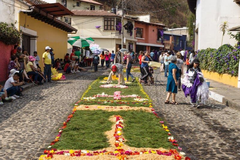 Locale che lavora ai alfombres, tappeti del fiore sulle vie cobbled per la processione San Bartolome de Becerra in Antigua immagine stock