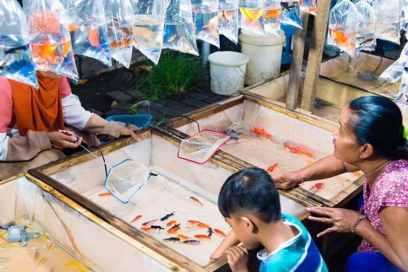 Locali che comprano pesce dorato al mercato di notte di Gianyar in Bali, Indonesia immagini stock