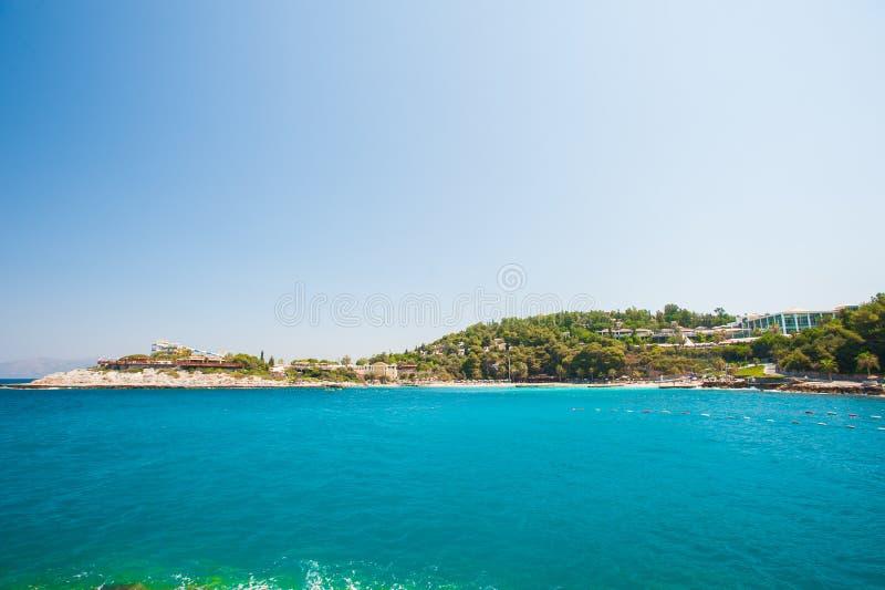 Località di soggiorno su acqua blu, spiaggia ad una parte immagine stock