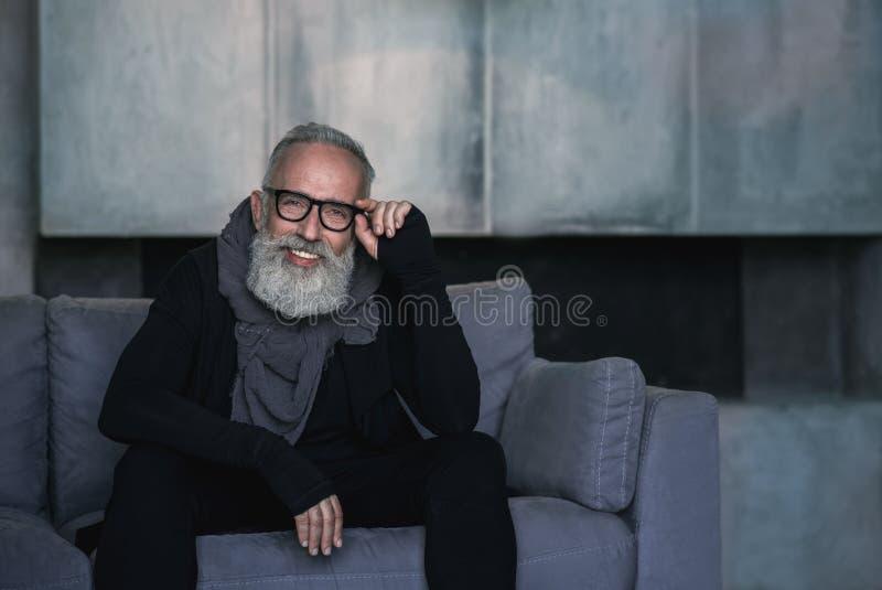 Localização madura não barbeado feliz no sofá imagens de stock