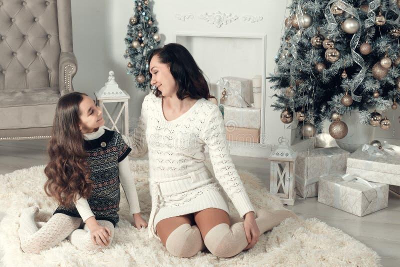 Localización de dos muchachas agradables, de la madre y de la hija en un piso en Christm imágenes de archivo libres de regalías