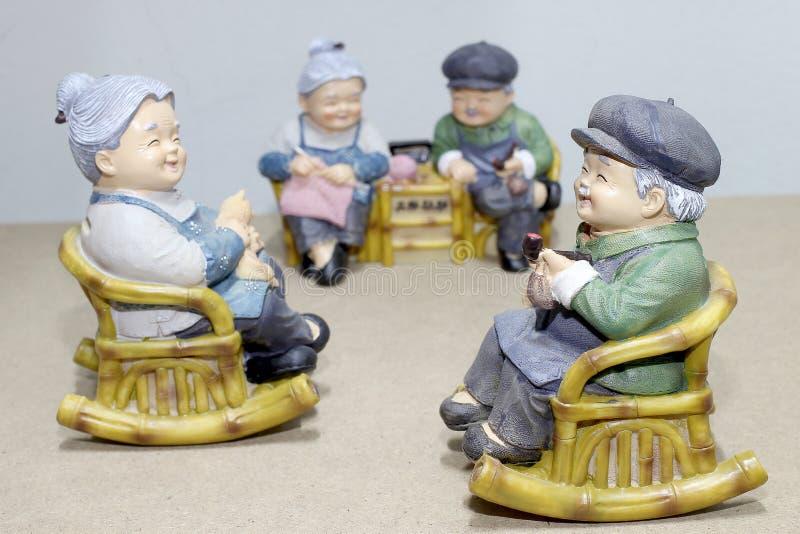 Localización preciosa de la muñeca del abuelo que oscila la silla de bambú en el fondo de madera - todavía vida fotos de archivo
