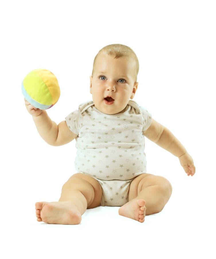 Localización seria del bebé y el jugar con la bola colorida Aislado en el fondo blanco imagen de archivo