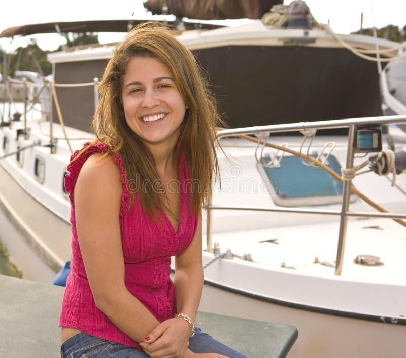 Localización sonriente de la muchacha al lado de un barco con el espacio de la copia imagen de archivo