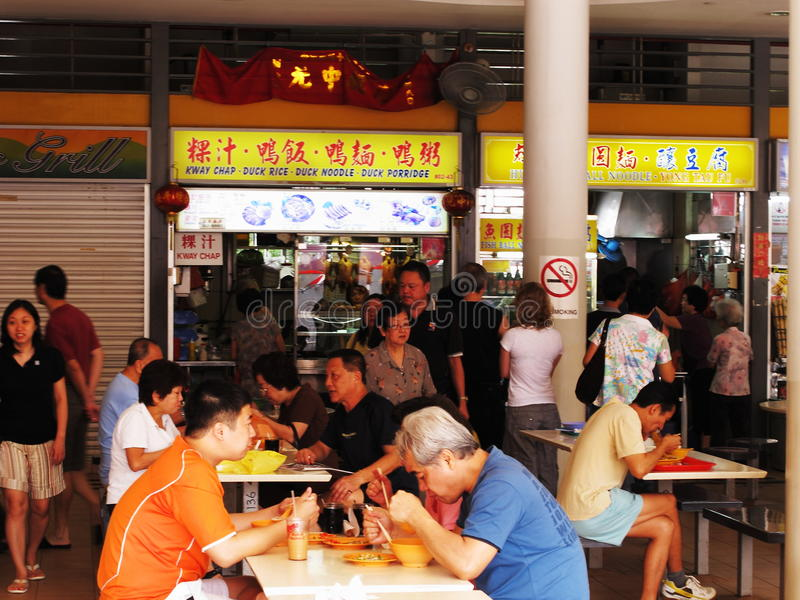 Locals em um centro do alimento do vendedor ambulante em Singapore fotografia de stock