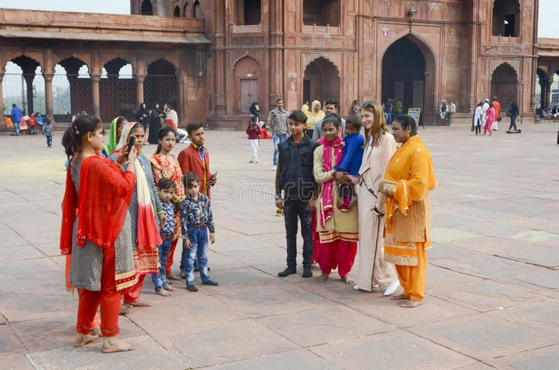 Locals at Jama Masjid taking pictures with foreign tourist. At the largest mosque in Asia royalty free stock photo