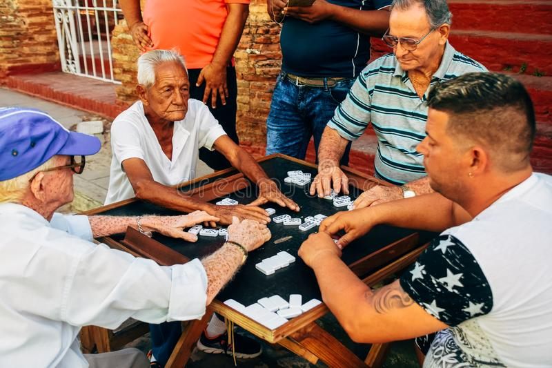 Locals playing dominoes in the streets of Trinidad, Cuba. 4 locals playing dominoes in the streets of Trinidad, Cuba stock photography