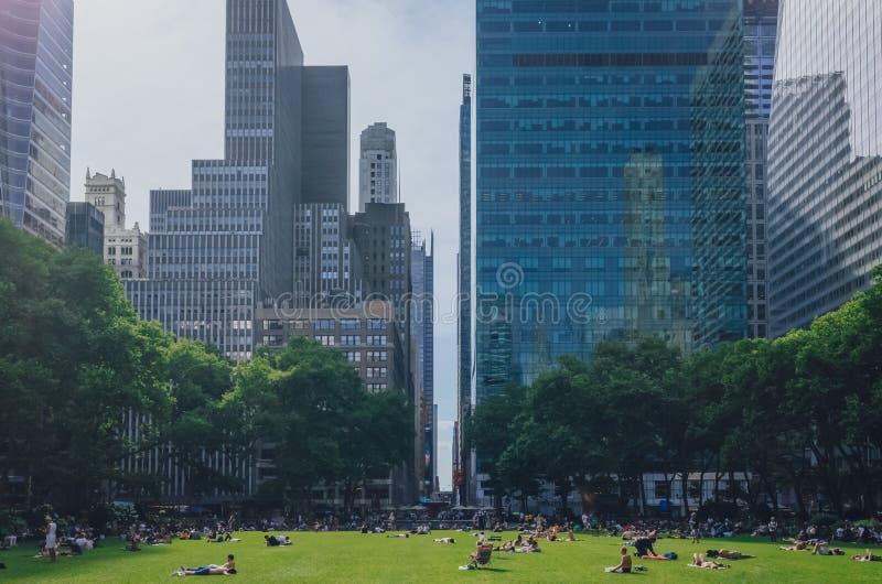 Locals que disfrutan de un día del comienzo del verano en Bryant Park entre rascacielos de Manhattan fotografía de archivo libre de regalías