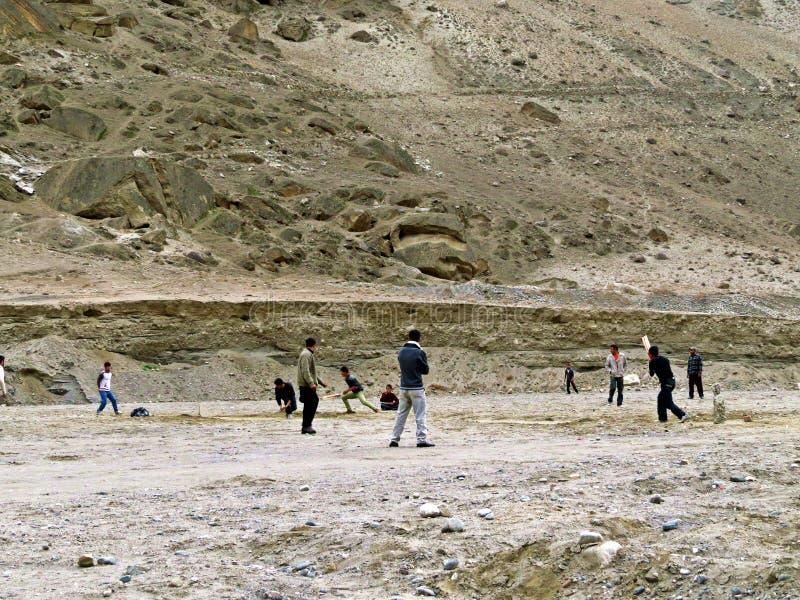 locals que juegan al grillo en Karimabad, valle de Hunza, carretera de Karakoram, Paquistán imagenes de archivo
