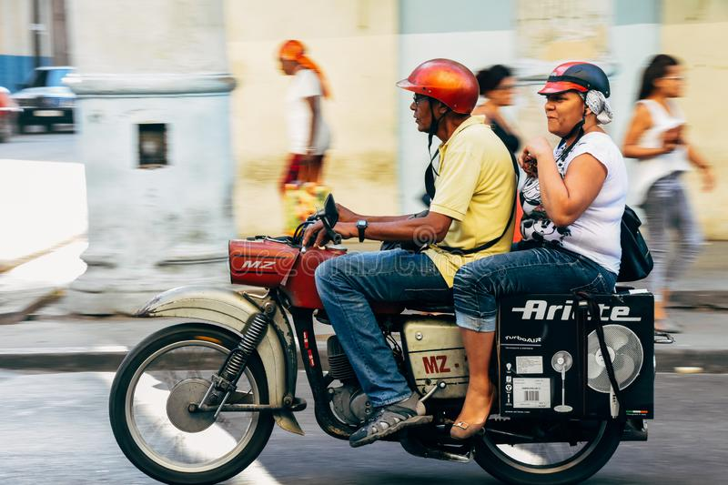 Locals riding a classic motorbike in Cuba. stock image