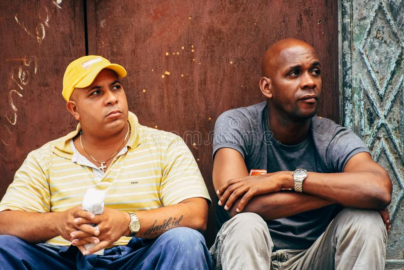 2 locals sit in the shade in Havana, Cuba. 2 locals sit in the shade to cool off in Havana, Cuba stock photo