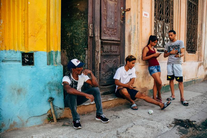 Locals sit and wait for a bus in Havana, Cuba. 4 locals sit and wait for a bus in Havana, Cuba royalty free stock photo