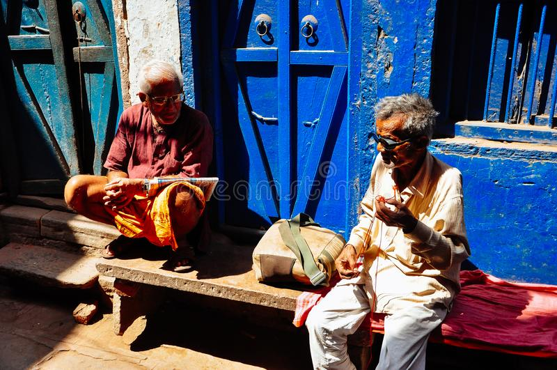 A locals talk in a alley in Varanasi, India. royalty free stock photos
