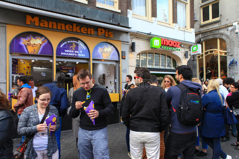Locals and tourist at Amsterdam's famous Manneken pis dutch fries. Fast food shop royalty free stock images