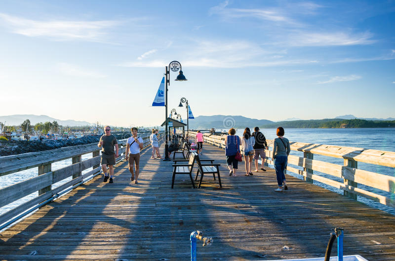 Locals and Tourists strolling along a Fishing Pier at Sunset royalty free stock image