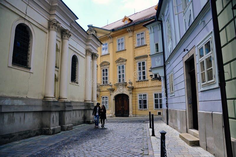 Locals walk in Old Bratislava, Slovakia. 2 locals walking the back streets in Old Bratislava, Slovakia stock image