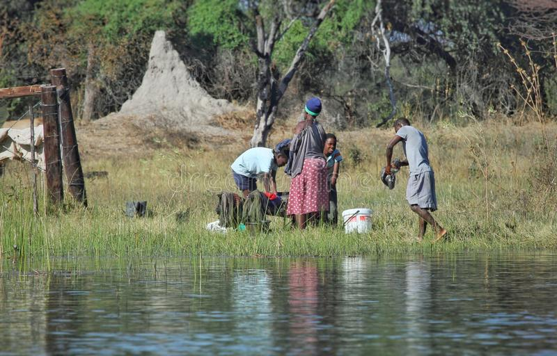 Locals washing up their own cloths at the riverside stock images