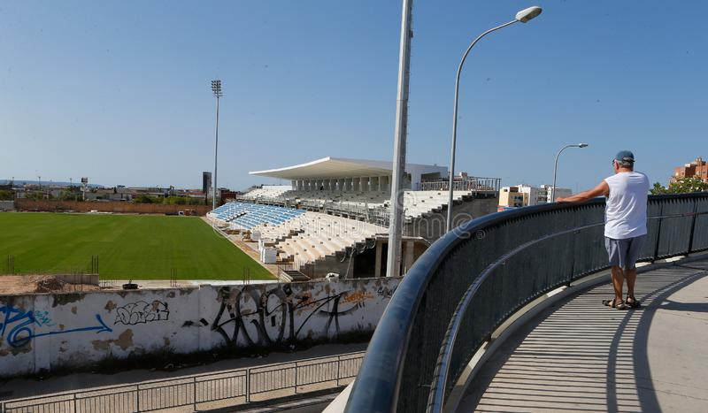 Locals watch the remodelation of the Balearic soccer stadium in Mallorca. Locals watch the remodelation and construction works of the Balearic soccer stadium in stock image
