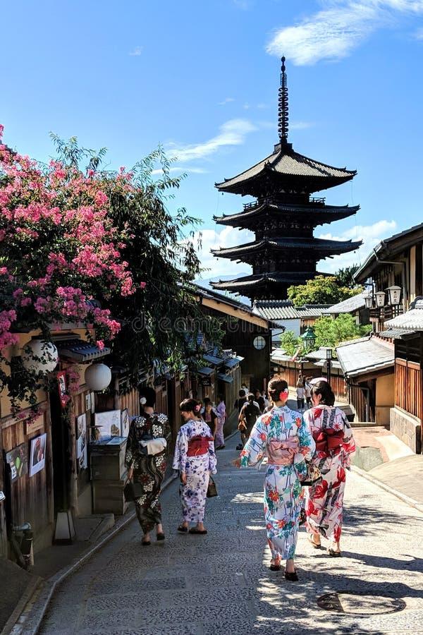 Locals y turistas vestidos para arriba en los kimonos, dando un paseo a través del distrito vibrante del geisha de Gion en Kyoto, imagen de archivo