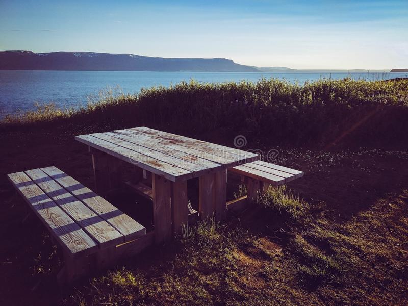 Camping wood table with views to icelandic fjord stock image