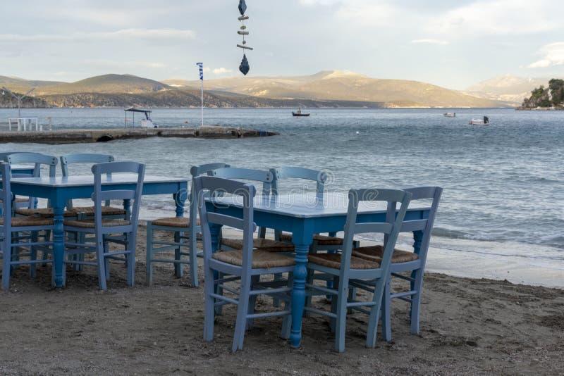 Locanda greca tradizionale con le tavole di legno sulla spiaggia sabbiosa vicino ai turisti aspettanti dell'acqua in Tolo, il Pel fotografie stock