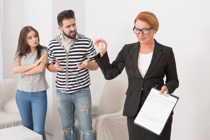 Locataires sans scrupules discutant avec l'agent immobilier, qui maintient des clés et des documents dans ses mains photographie stock libre de droits