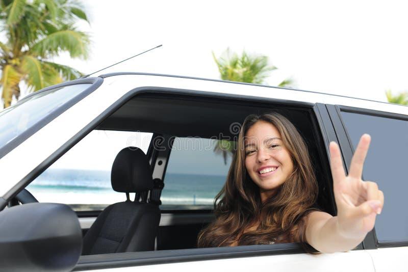 Location de voiture : femme heureuse dans son véhicule près de la plage photos stock