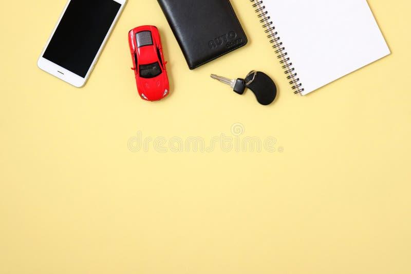 Location de voiture ou concept de partager Smartphone, permis de conduire, voiture de jouet et cl? d'automobile sur le fond jaune photographie stock