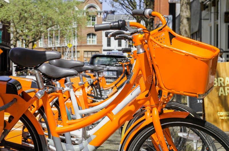 Locations oranges de bicyclette dans la ville images stock