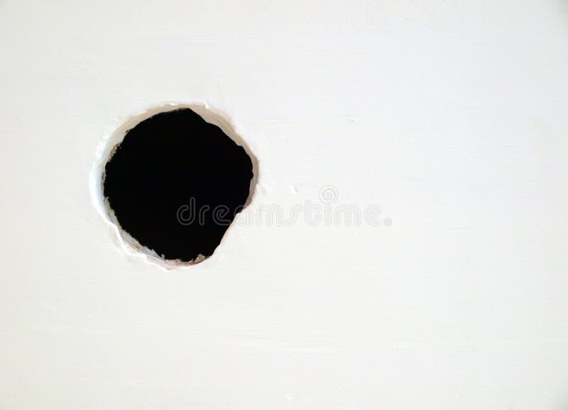 Loch auf der weißen Wand lizenzfreie stockfotografie
