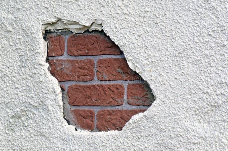 Loch in einer Backsteinmauer stockfotografie