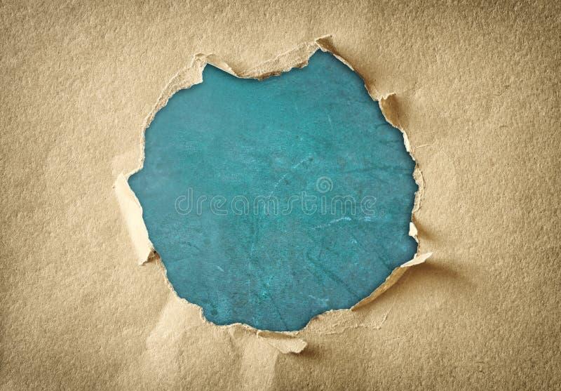 Loch gemacht von heftigem Papier über strukturiertem blauem Hintergrund lizenzfreie stockbilder
