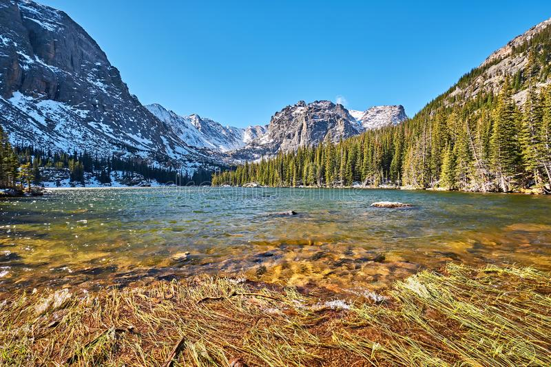 The Loch Lake, Rocky Mountains, Colorado, USA. The Loch Lake with rocks and mountains in snow around at autumn. Rocky Mountain National Park in Colorado, USA stock photography