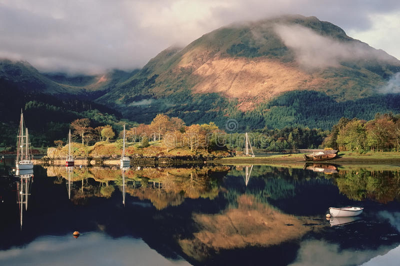 Loch Leven moorings, Scotland. The first rays of dawn strike this calm mooring area on loch Leven, North Ballachulish, in Scotland. Very close to Glencoe and the stock photo