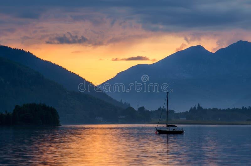 Loch Leven. Sailing boat on Loch Leven in sunsetl, Glencoe, Scotland royalty free stock photo