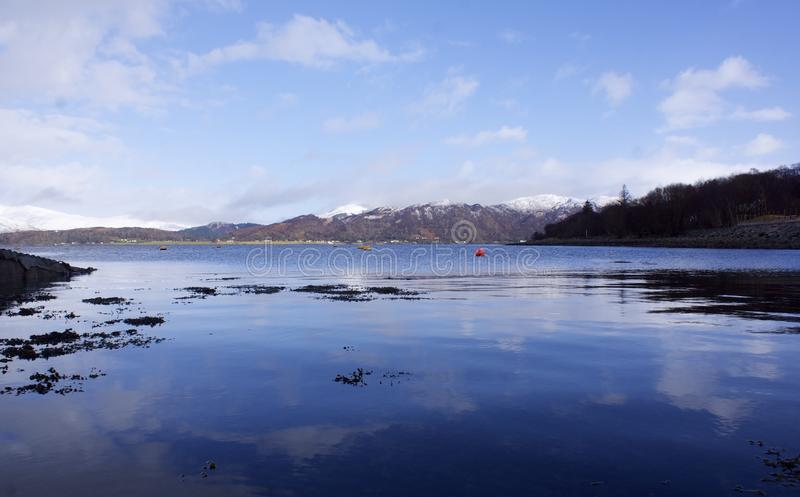 Loch Linhe and Ben Nevis. A reflective view of Ben Nevis across Loch Linhe from Kentallen. This shot is taken in February and shows the snow on the Scottish stock photos
