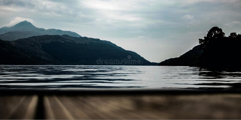 Loch Lomond con las montañas en el fondo foto de archivo