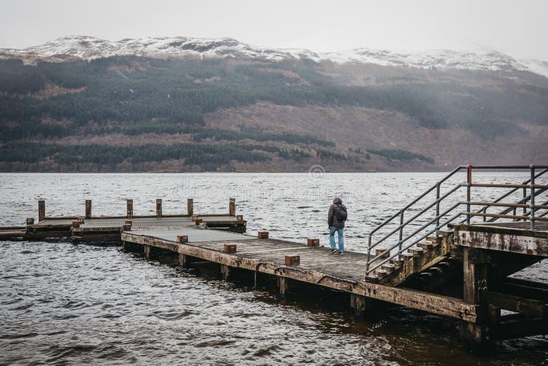 Man walking on a pier on Loch Lomond in Scotland stock image