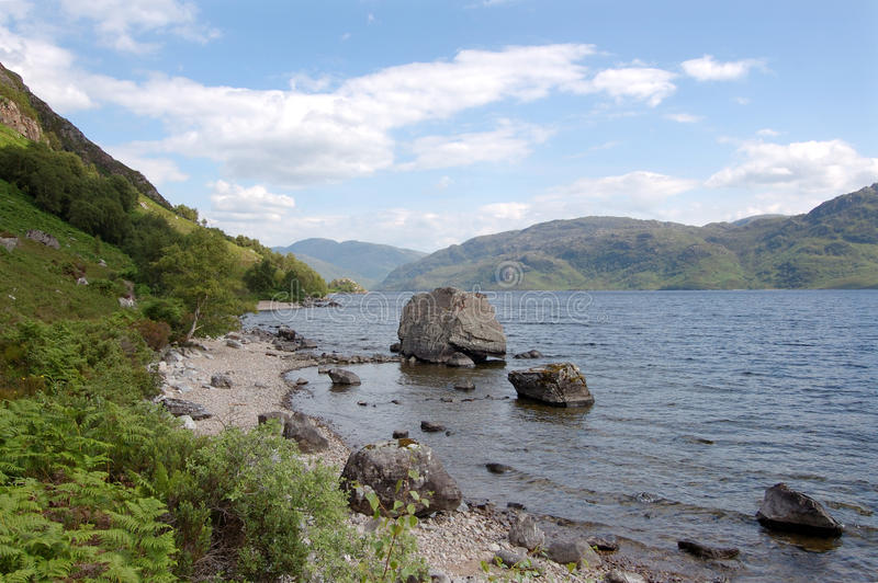 Loch Morar looking east with big rock. Looking toward the south Morar hills from the north shore of Loch Morar, Scotland with alarge rock on the loch foreshore stock images