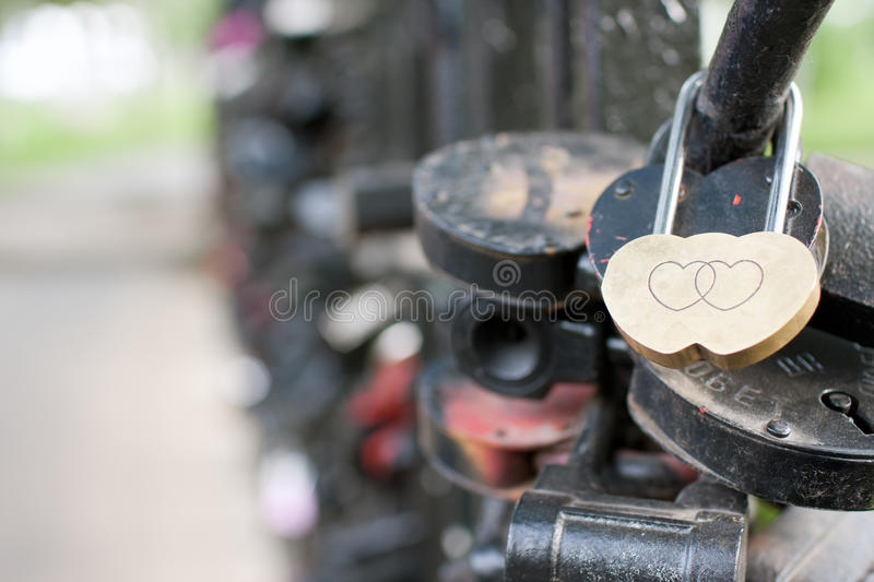 Lock on the bridge. Gold lock in the form of hearts hanging on the bridge next to the other locks royalty free stock photography