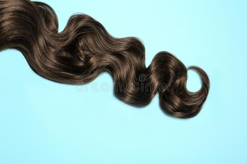 Lock of brown wavy hair on color background. Top view royalty free stock image