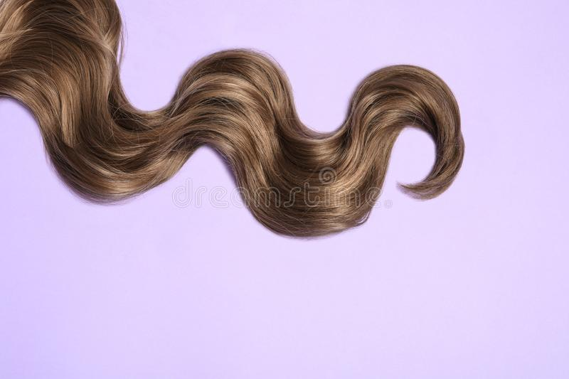 Lock of brown wavy hair on color background. Space for text. Lock of brown wavy hair on color background, top view. Space for text stock photos