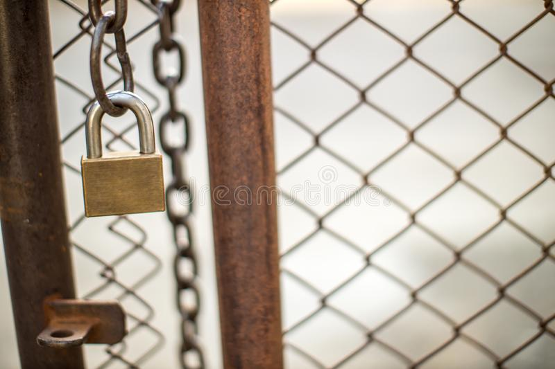 Lock on a chain link security fence. Chicken wire fence gate is locked with a chain and a padlock stock photography