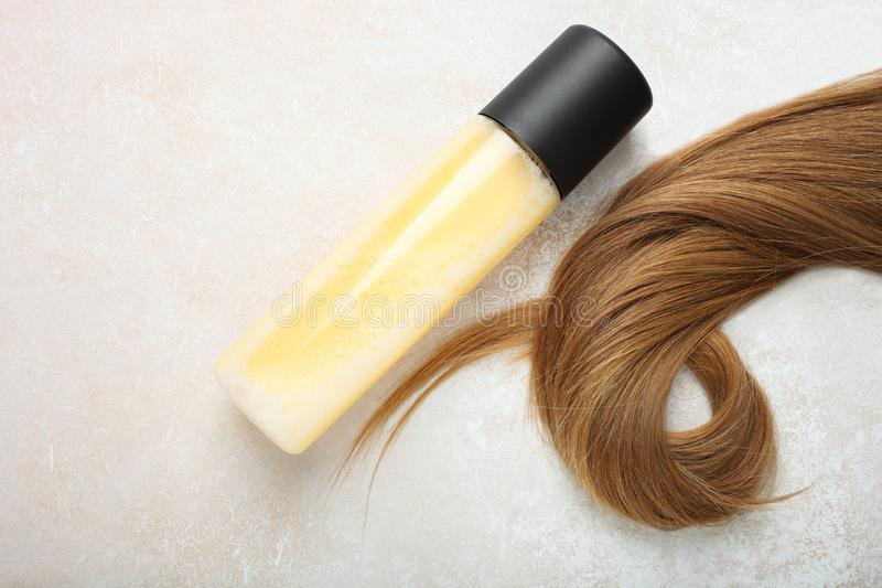 Female light brown hair and hair spray. Lock of female light brown hair and hair spray on neutral background. Top view stock photos