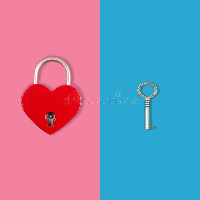 Lock in the form of a heart on a pink background and a key on a blues. Lock in the form of a heart on a pink background and a key on a blue, a symbol of love stock photography