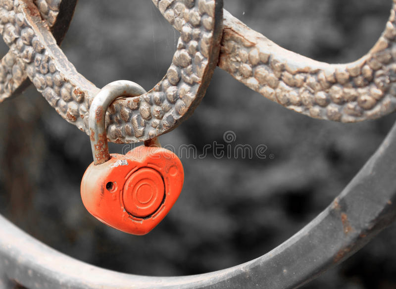 Lock in heart shape on the railing of bridge - a symbol of happy and long married life of bride and groom. Conceptual photo royalty free stock images