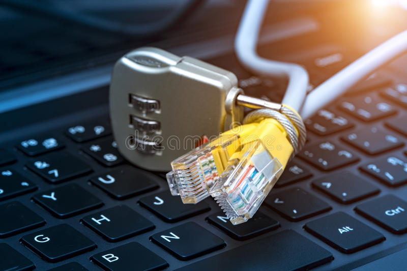 Lock and network cable with computer keyboard background. The concept of computer security stock photos