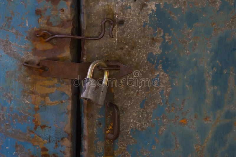 Lock and old hook. Blue metal door with old lock in grungy style closeup royalty free stock image
