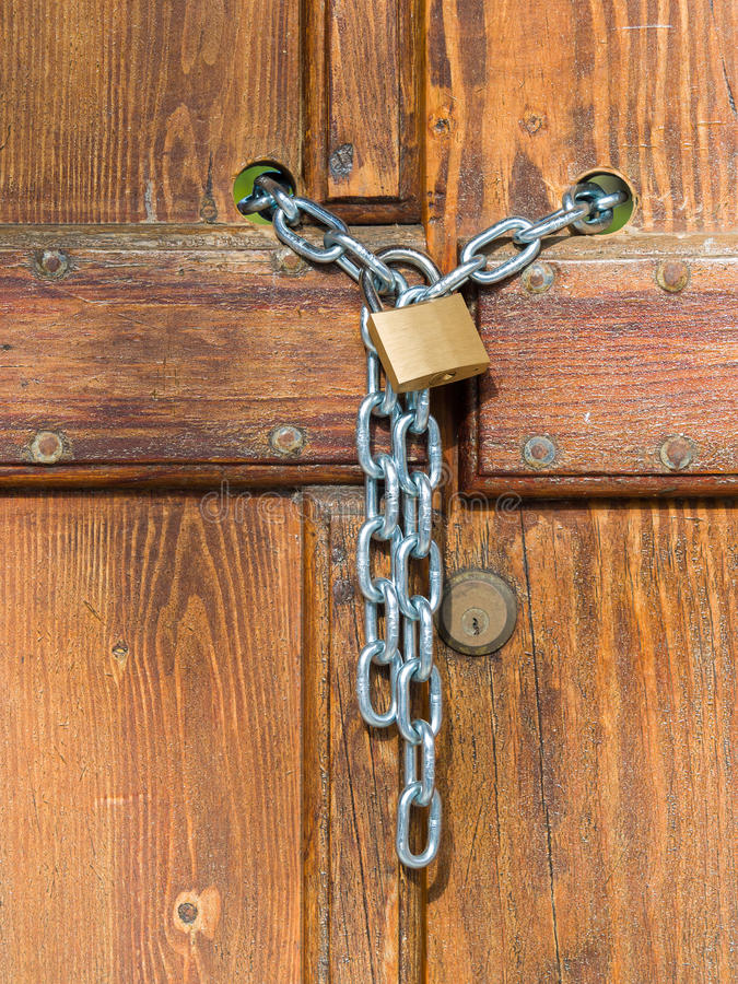 Lock and shiny chain closing a wooden garden gate. Lock and shiny rings chain closing a wooden garden gate stock photography