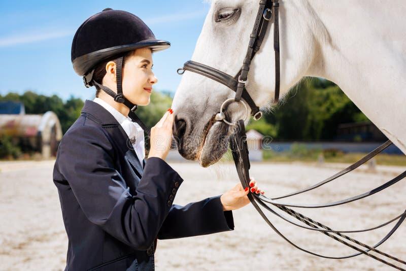 Lockande skicklig ryttarinna som ser in i ögon av hennes vita häst royaltyfri foto